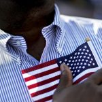 A candidate for citizenship holds the American flag